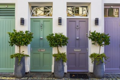 Two residential properties, one with a green front door and one with a purple front door
